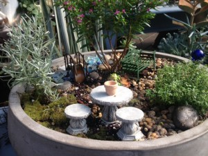Miniature garden, gray round bow, stone table and stools, green bench, bridge, heather tree