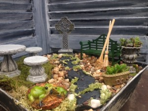 Miniature garden with Celtic cross, green metal bench, stone table & chairs