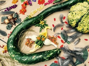 A snake gourd encircles smaller gourds and bittersweet with heuchera leaves, corn kernels and bulbs above...